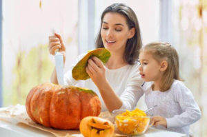 Photo of mother and daughter carving pumpkins